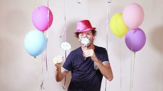 Happy man with pink shiny hat dancing in photo booth
