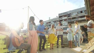 Happy people dancing and playing guitar at the rooftop party on sunny day
