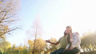 Happy young couple having fun while listening to music on headphones in park, slow motion, graded
