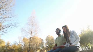 Happy young couple having fun while listening to music on headphones in park, slow motion