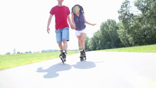Happy young couple rollerblading on a wonderful sunny day in park, doing tricks
