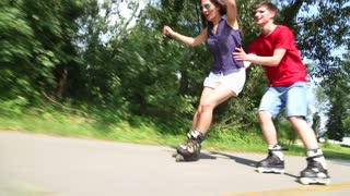 Happy young couple rollerblading on a wonderful sunny day in park, holding her waist