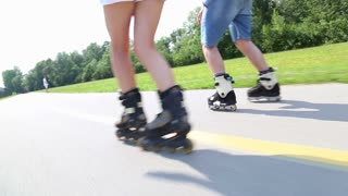 Happy young couple rollerblading on a wonderful sunny day in park, view of legs