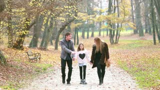 Happy young family holding hands and walking in park on beautiful autumn day, graded