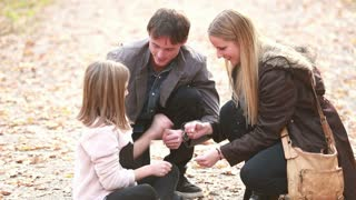 Happy young family sitting on pathway in park and playing games