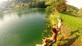 Happy young friends jumping into river on beautiful sunny day, graded, in slow motion