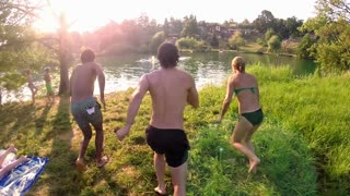 Happy young friends running and jumping into river on beautiful sunny day, graded, in slow motion