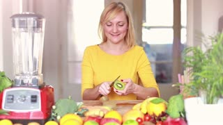 Happy young woman peeling skin off kiwifruit, graded