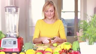 Happy young woman peeling skin off kiwifruit, in slow motion, graded
