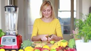 Happy young woman peeling skin off kiwifruit