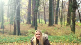 Happy young woman smiling and throwing leaves in the air at park, slow motion, graded