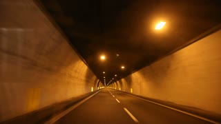 HD timelapse of car driving on highway at night through tunnels.