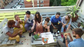 High angle view of friends eating pizza on the rooftop terrace