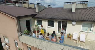 High angle view of group of friends hanging out at rooftop party