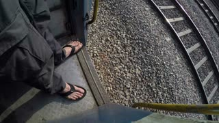 High angle view of human feet by open door of moving train.