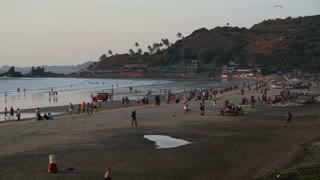 High angle view of people at sandy beach in Goa at sunset.