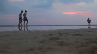 HIKKADUWA, SRI LANKA - FEBRUARY 2014: Family walking on beach and throwing child in the air. Hikkaduwa is famous for its beautiful beaches.