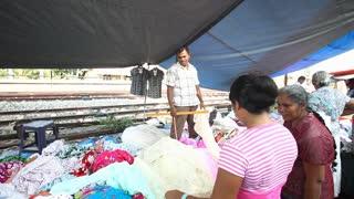 HIKKADUWA, SRI LANKA - FEBRUARY 2014: Local salesman showing and arranging textile at Hikkaduwa market. Hikkaduwa Sunday market is known for its wide range of supplies.