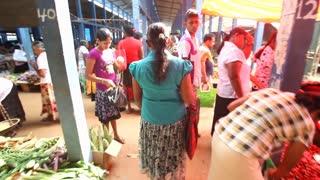 HIKKADUWA, SRI LANKA - FEBRUARY 2014: Local woman passing by and browsing at Hikkaduwa market. Hikkaduwa Sunday market is known for its wide range of supplies.