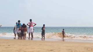 HIKKADUWA, SRI LANKA - FEBRUARY 2014: Locals enjoying the beach and playing in the surf. Waves are very strong and not many locals swim.