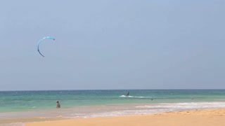 HIKKADUWA, SRI LANKA - FEBRUARY 2014: Man kite surfing from  sandy beach.