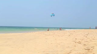 HIKKADUWA, SRI LANKA - FEBRUARY 2014: Man playing with kite on sandy beach.