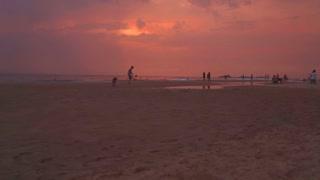 HIKKADUWA, SRI LANKA - FEBRUARY 2014: People playing sports on the sandy beach at sunset.
