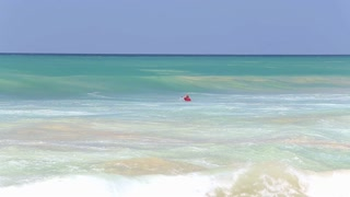 HIKKADUWA, SRI LANKA - FEBRUARY 2014: The view of the surfer surfing in the ocean on Hikkaduwa beach. Hikkaduwa is famous for its beautiful beaches.