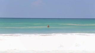 HIKKADUWA, SRI LANKA - FEBRUARY 2014: The view of the waves on Hikkaduwa beach while a person is enjoying the ocean. Hikkaduwa is famous for its beautiful beaches.