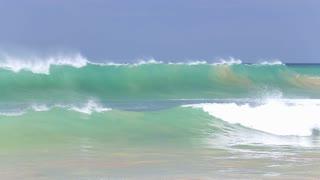 HIKKADUWA, SRI LANKA - FEBRUARY 2014: The view of the waves on Hikkaduwa beach while the surfer is enjoying the ocean. Hikkaduwa is famous for its beautiful beaches.