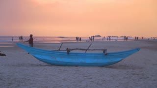 HIKKADUWA, SRI LANKA - FEBRUARY 2014: Traditional fishing boat on Hikkaduwa beach at sunset. Hikkaduwa is famous for its beautiful beaches.
