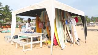 HIKKADUWA, SRI LANKA - FEBRUARY 2014: View of a surf stand and local man working there on Hikkaduwa beach. Hikkaduwa is famous for its beautiful beaches.