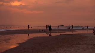 HIKKADUWA, SRI LANKA - FEBRUARY 2014: View of Hikkaduwa beach at sunset, while waves are splashing and people are enjoying themselves. Hikkaduwa is famous for its beaches.