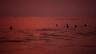 HIKKADUWA, SRI LANKA - FEBRUARY 2014: View of Hikkaduwa beach at sunset, while waves are splashing and people are enjoying themselves in the ocean. Hikkaduwa is famous for its beaches.
