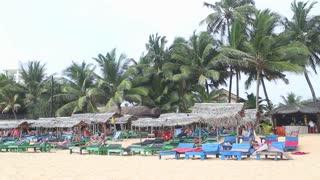 HIKKADUWA, SRI LANKA - FEBRUARY 2014: View of Hikkaduwa beach bar while wind is blowing and palms are swaying in the wind. Hikkaduwa is famous for its beautiful beaches.