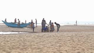 HIKKADUWA, SRI LANKA - FEBRUARY 2014: View of Hikkaduwa beach while kids are playing and people are walking on the beach. Hikkaduwa is famous for its beautiful beaches.
