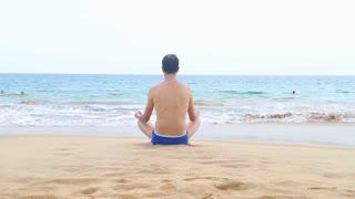 HIKKADUWA, SRI LANKA - FEBRUARY 2014: View of Hikkaduwa beach while waves are splashing and a man is meditating near the ocean. Hikkaduwa is famous for its beautiful beaches.