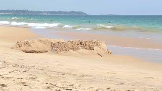 HIKKADUWA, SRI LANKA - FEBRUARY 2014: View of Hikkaduwa beach while waves are splashing and people are enjoying themselves in the ocean.