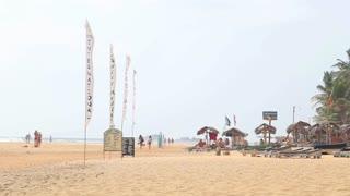 HIKKADUWA, SRI LANKA - FEBRUARY 2014: View of Hikkaduwa beach while wind is blowing in flags on shore.