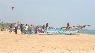 HIKKADUWA, SRI LANKA - FEBRUARY 2014: View of locals standing and sitting on boat on Hikkaduwa beach. Hikkaduwa is famous for its beautiful beaches.