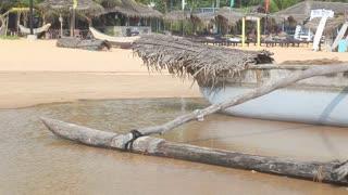 HIKKADUWA, SRI LANKA - FEBRUARY 2014: View of the boat on Hikkaduwa beach surrounded by water. Hikkaduwa is famous for its beautiful beaches.