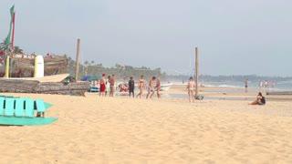 HIKKADUWA, SRI LANKA - FEBRUARY 2014: Young people playing volleyball on the beach. Hikkaduwa is famous for its beautiful beaches.