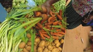 HIKKADUWA, SRI LANKA - MARCH 2014: Customer choosing vegetables at the Sunday market in Sri Lanka known for its varied produce.