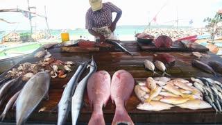 HIKKADUWA, SRI LANKA - MARCH 2014: Local man cutting fish at Hikkaduwa Sunday market, known for its wide range of fresh and varied produce.