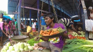 HIKKADUWA, SRI LANKA - MARCH 2014: Local man sitting and weighing his vegetables at market.