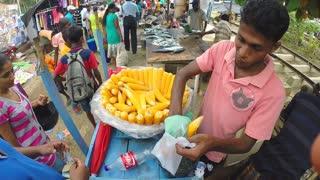 HIKKADUWA, SRI LANKA - MARCH 2014: Local salesman selling cooked corn at the Sunday market in Sri Lanka.