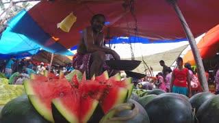HIKKADUWA, SRI LANKA - MARCH 2014: Man selling decorated watermelon at the Sunday market in Sri Lanka