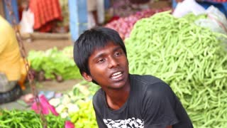 HIKKADUWA, SRI LANKA - MARCH 2014: Portrait of local young man selling vegetables at Hikkaduwa Sunday market, known for its wide range of fresh and varied produce.