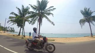 HIKKADUWA, SRI LANKA - MARCH 2014: Slow motion of the view on the beautiful beach with palm trees from moving vehicle.