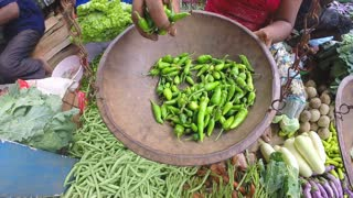 HIKKADUWA, SRI LANKA - MARCH 2014: View of woman weighing chillis at the Sunday market in Sri Lanka.